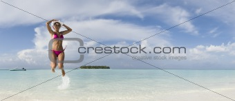 Woman jump in lagoon of Ihuru Island Maldives