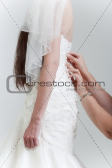 bride with long dark hair getting dressed on her wedding day - isolated on gray