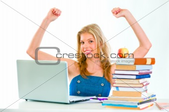 Smiling beautiful girl sitting at table and rejoicing success