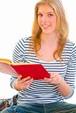 Happy teen girl reading book