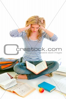 Teen girl sitting on floor among schoolbooks and studying hard