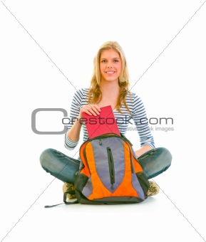 Sitting on floor happy teenager getting book from schoolbag