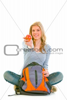 Cheerful teenager sitting on floor with schoolbag and giving apple