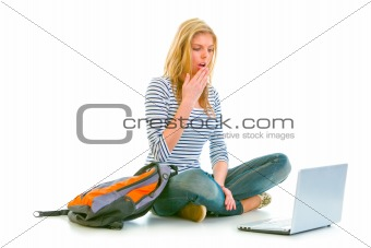 Amazed teen girl sitting on floor with backpack and looking on laptop