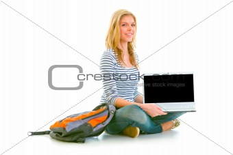 Smiling teen girl sitting on floor and showing laptops blank screen