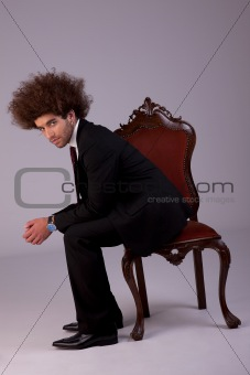 handsome business man, sitting on a chair, studio shot.