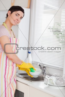 Woman washing the dishes looking into the camera