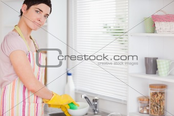 Brunette Woman washing the dishes looking into the camera