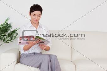 Beautiful brunette woman reading a magazine