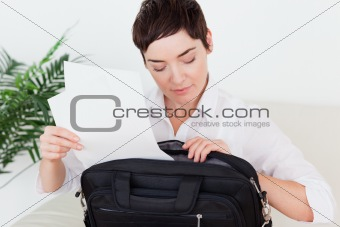 Businesswoman putting some papers in her bag