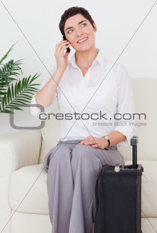 Beautiful woman with a suitcase and a phone
