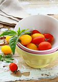 Stack of bowls and fresh tomatoes on a wooden table