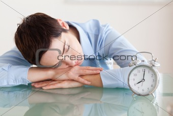 Sleeping woman with her head on the desk next to an alarmclock