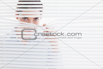 Curious cute Woman peeking out of a window