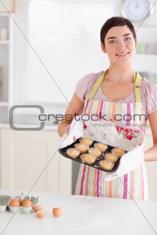 Beautiful brunette woman showing muffins