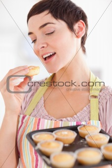 Smiling brunette woman showing muffins while eating one
