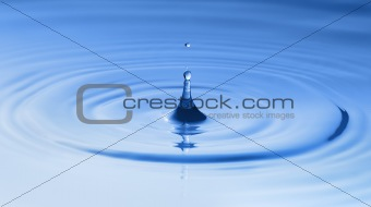 Clean blue drop of water splashing in clear water. Abstract blue