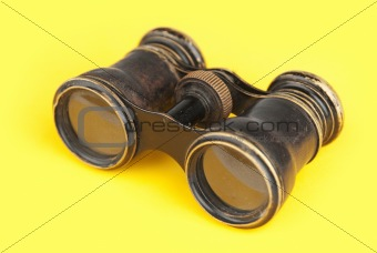 Old binoculars on yellow background