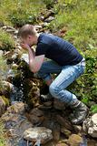 Young man taking a refreshment in the mountains