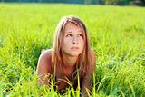 Portrait of young beautiful woman lying on green grass