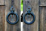 ancient wooden gate with door knocker rings