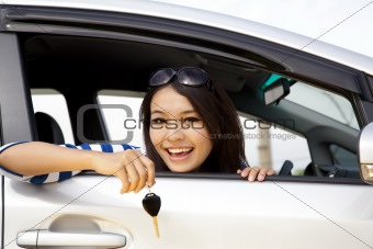 young happy woman in car showing the key