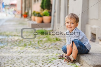 little boy sits on the doorstep on a city street