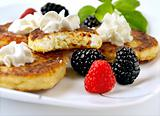 Curd pancakes with berries .