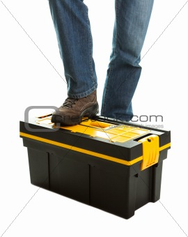 Close-up of repairman standing on toolbox