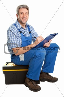 Confident service man sitting on toolbox