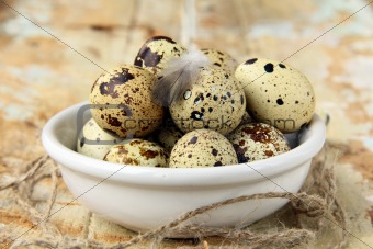quail eggs in a bowl on a wooden table