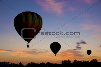 Hot-air balloons floating against a reddish dawn sky