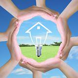 light bulb model of a house in women hand making a circle