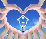 light bulb model of a house in women hands making a symbol of love