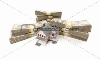 Small House with Stacks of Hundred Dollar Bills Isolated on a White Background.