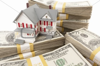 Small House with Stacks of Hundred Dollar Bills on White.