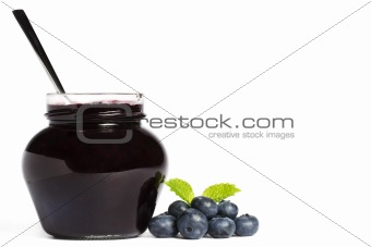 jam jar with blueberry jam a spoon and blueberries with a leaf melissa