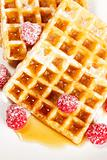 sugar covered raspberries on waffles with syrup