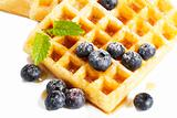 waffles with sugar covered blueberries and syrup from top