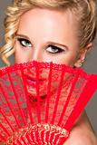 Portrait of girl closing face with textile fan. Retouched