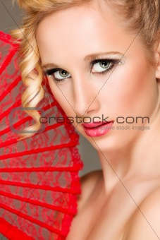 Portrait of pretty girl with textile fan in hand. Retouched
