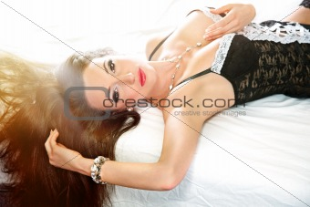 Portrait of sensual woman with long brown hair lying on bed
