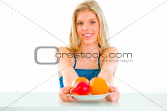 Cheerful lovely girl sitting at table with plate of fruits