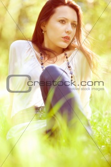 Thoughtful pretty girl sitting on green grass