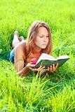 Young woman lying in grass reading book an nectarine in his hand