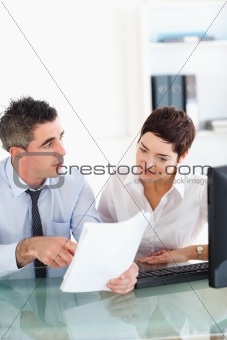 Portrait of coworkers talking about a document