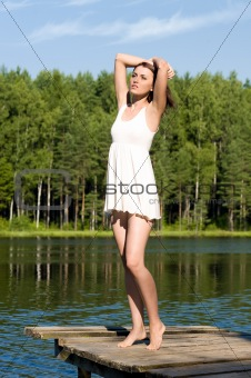 beautiful woman is standing in the lake. Summer time