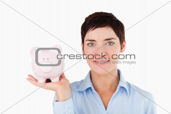 Close up of a female worker holding a piggy bank