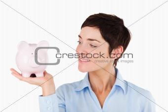 Close up of an office worker holding a piggy bank