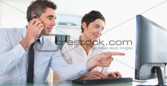 Businessman showing something to his coworker on a computer